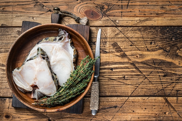 Raw wolffish or wolf fish fillet in a wooden plate. wooden background. top view. copy space.
