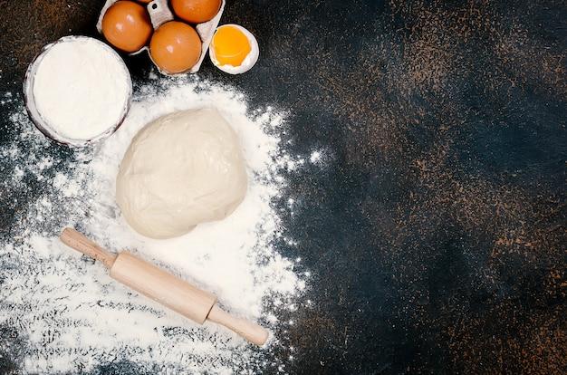 어두운 테이블에 그릇과 재료, 계란, 밀가루, 밀 귀에 생 효모 반죽