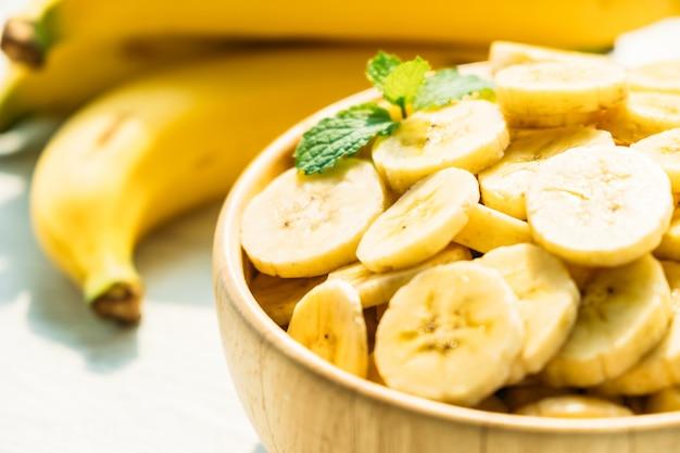 木製のボウルに生の黄色のバナナのスライス 無料写真