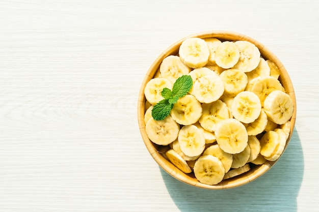 Raw yellow banana slices in wooden bowl