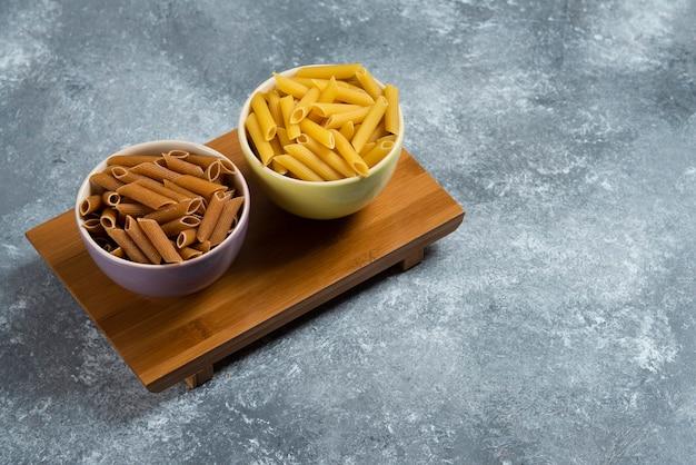 Pasta di semola gialla e marrone cruda sulla tavola di legno.