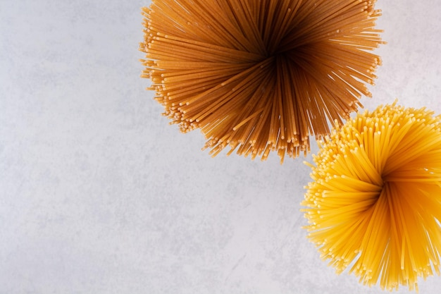 Raw yellow and brown spaghetti on white table.