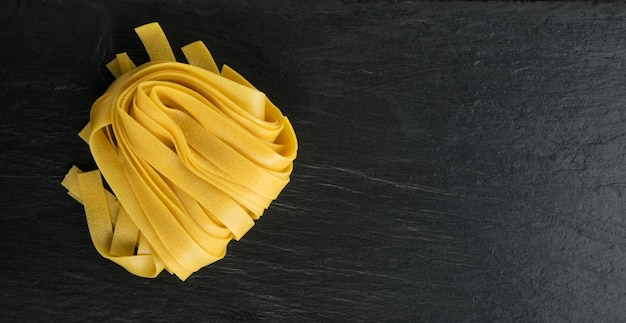生の黄色いイタリアンパスタフェットチーネ、フェットチーネ、またはタリアテッレがクローズアップ。卵の自家製ドライリボンヌードル、長く巻いたマカロニ、または未調理のスパゲッティの上面図