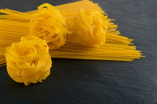 生の黄色いイタリアンパスタフェットチーネ、フェットチーネ、またはタリアテッレがクローズアップ。卵の自家製ドライリボンヌードル、長く巻いたマカロニ、または未調理のスパゲッティ