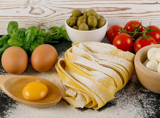 生の黄色いイタリアンパスタパッパルデッレ、フェットチーネ、またはタリアテッレがクローズアップ。卵の自家製麺の調理プロセス、長い巻きマカロニ、またはオリーブ、トマト、バジルを使った未調理のスパゲッティ