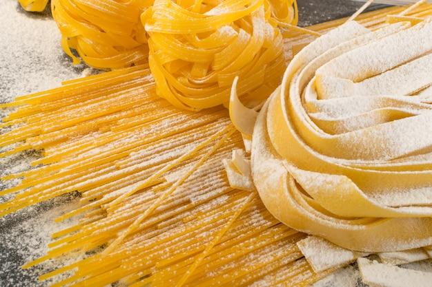 生の黄色いイタリアンパスタパッパルデッレ、フェットチーネ、またはタリアテッレがクローズアップ。卵の自家製麺の調理プロセス、長い巻きマカロニまたは未調理のスパゲッティ