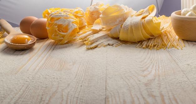 生の黄色いイタリアンパスタパッパルデッレ、フェットチーネ、またはタリアテッレが卵でクローズアップします。長いマカロニまたはスパゲッティを使った自家製麺の調理プロセス