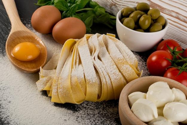 生黄色のイタリアンパスタパッパルデッレ、フェットチーネ、タリアテッレは、卵と一緒にクローズアップ。