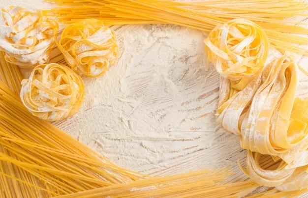 Сырая желтая итальянская паста паппарделле, феттучини или тальятелле текстуры