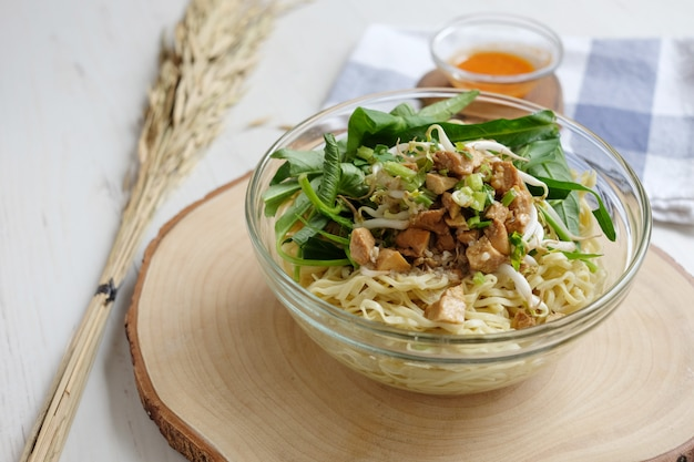 Raw yellow noodles with bean sprouts leaf and tofu on the bowl