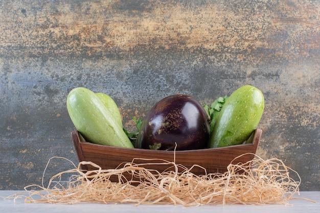 Zucchine crude e melanzane in cassetta di legno. foto di alta qualità