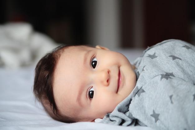 笑う赤ちゃん。白い部屋のベッドの上でrawう小さな赤ちゃん。彼の顔の興味と疑問に思った。ヨーロッパ人。赤ちゃんは驚いた。