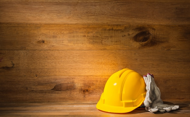 Ray of light falling on engineer or foreman safety helmet and gloves on wooden table