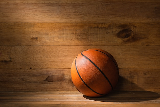 Ray of light falling on old basketball on wooden floor