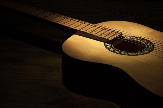 A ray of light falls on an acoustic guitar lying on a wooden textured background.