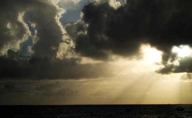 暗い雲の切れ間から輝く光線。雲と劇的な空。