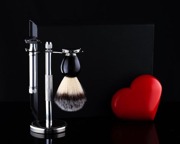 스탠드와 블랙 박스의 면도기와 브러시, 검은 색 ackground의 붉은 심장