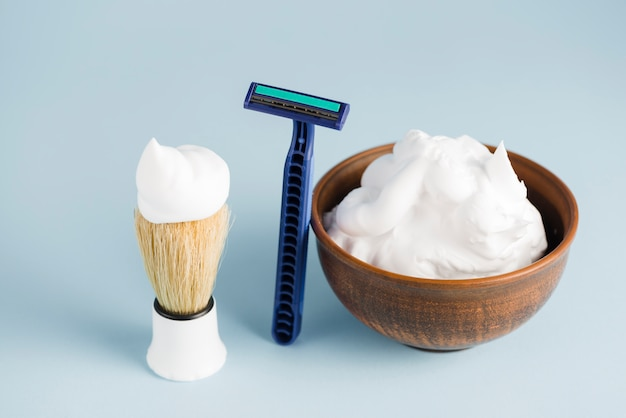 Razor; shaving brush and bowl of foam against blue backdrop