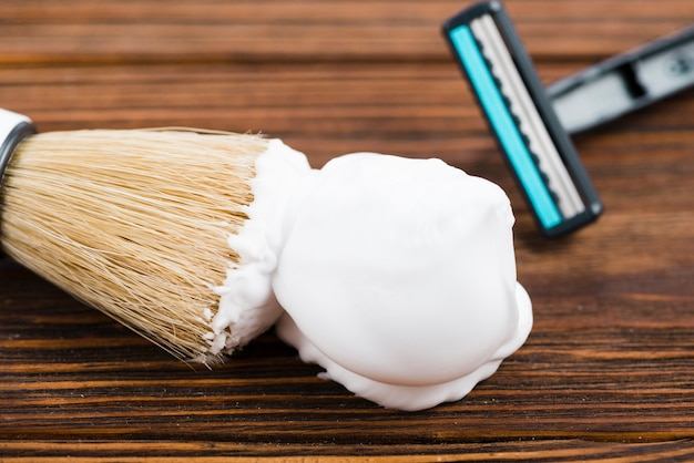 Razor and shaving brush with foam on wooden background