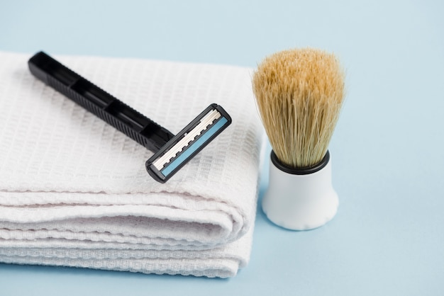 Razor on white folded napkin and classic shaving brush against blue background