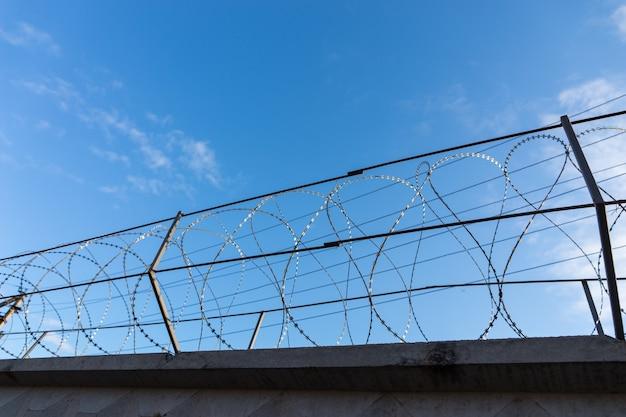백그라운드에서 맑은 푸른 하늘과 감옥 또는 기타 높은 보안 시설에서 보안 울타리의 상단을 따라 면도기 와이어