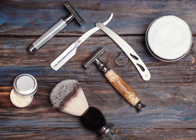 Бритвы, щетка, бальзам и пена на деревянном столе.