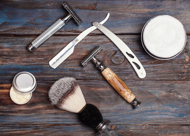 Razors, brush, balsam and foam on a wooden table.