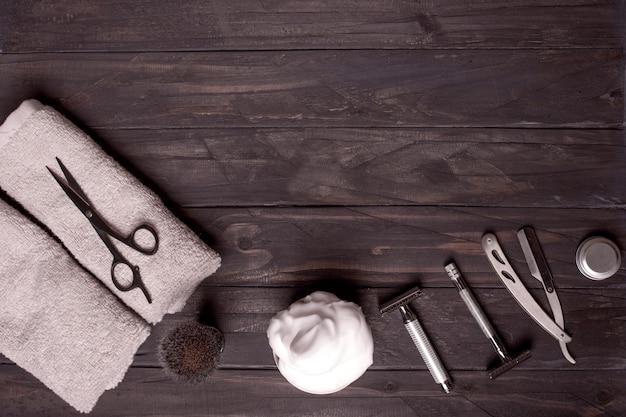Бритвы, щетка, бальзам, духи, полотенца и ножницы на деревянном фоне.