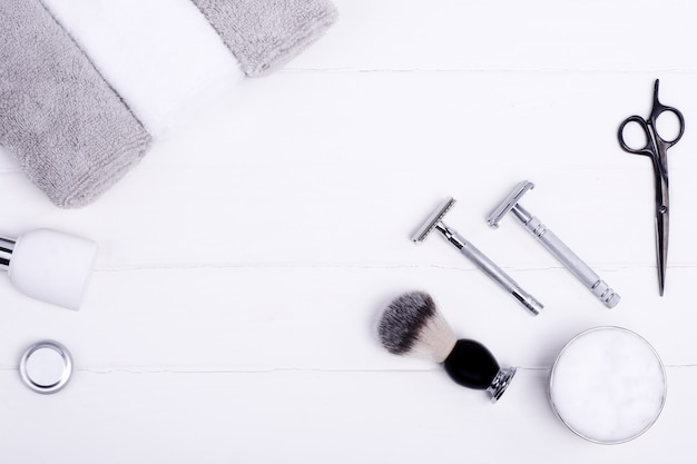 Razors, brush, balsam, perfume, towels and scissors  on a wood background.