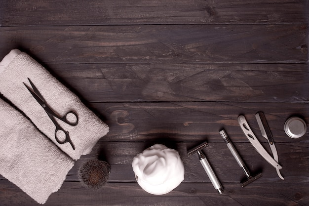 Razors, brush, balsam, perfume, towels and scissors  on a wooden background.