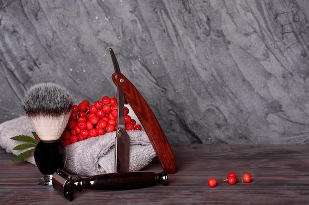 Бритвы, щетка, полотенца и рябина на деревянном фоне.