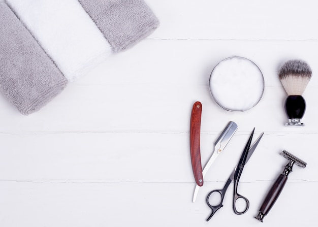 Razors, brush, towels and scissors on a wood background.