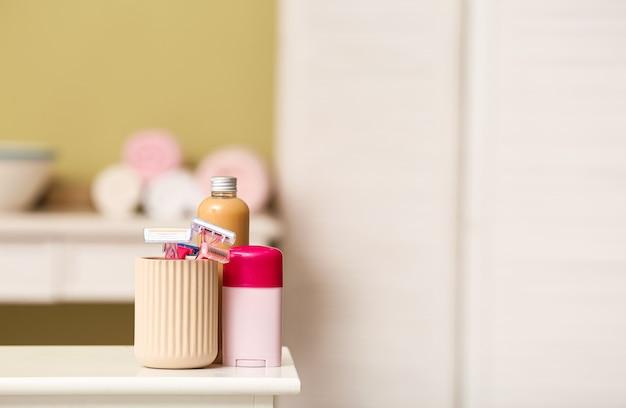 Бритвы для удаления волос с косметикой на столе в ванной комнате
