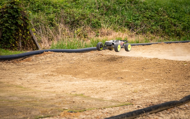 Rc truggy in the air after launching from a jump on the track