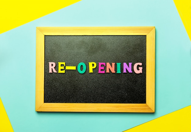 Мини-доска с надписью re opening на разноцветном фоне