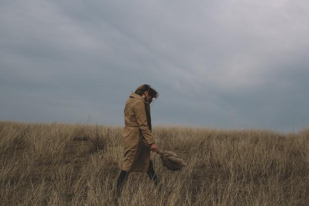 秋の草が乾いた野原で中立的な服を着て、花の咲くreの花束を手に持っている女性。ファッションの肖像画と風が彼女の髪を吹く