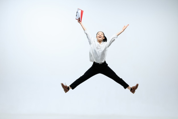 Reach new heights for your family. happy woman working at office, jumping and dancing in casual clothes or suit isolated on white studio background. business, start-up, working open-space concept.