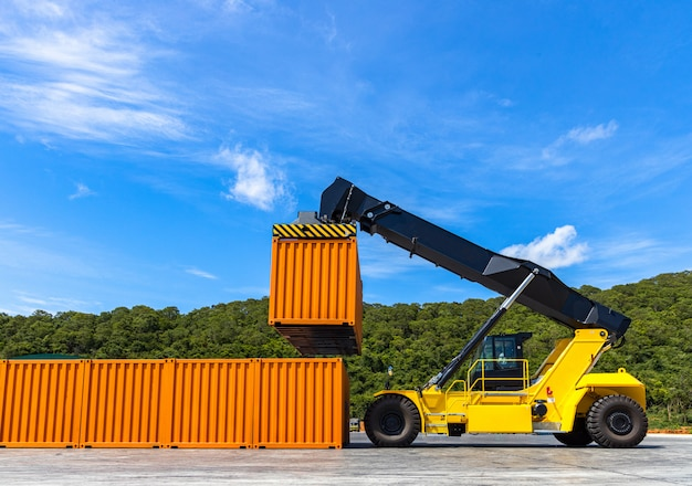 Reach stacker yellow forklift truck handling shipping container in business import