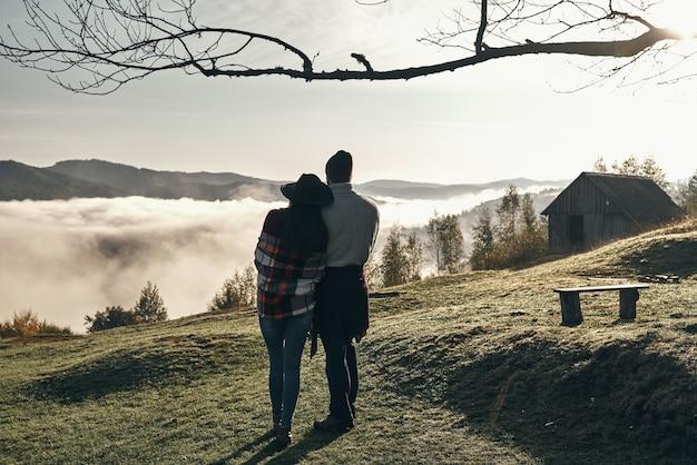 ピークに達した。山脈の完璧な景色を楽しみながら抱きしめる若いカップルの全身背面図