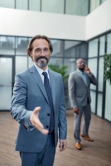 Протягивая руку. зрелый седой бизнесмен протягивает руку коллеге во время приветствия