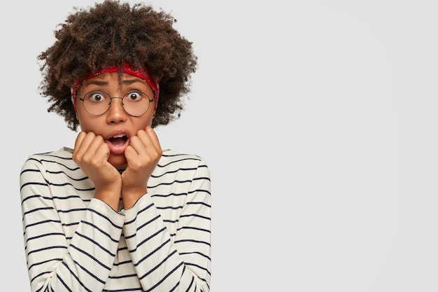 反応と感情の概念。ストレスのたまる恥ずかしい怖い女性が眼鏡を通して目を大きく開いて見つめる