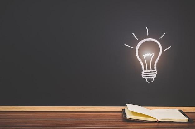 本を読むコンセプト黒板の電球のシンボルはアイデアを表しています