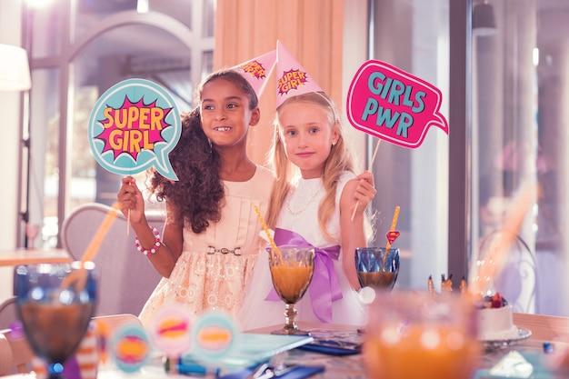 女の子を読んでください。パーティーハットをかぶって、面白い看板を持って笑っているかなり長い髪の女の子