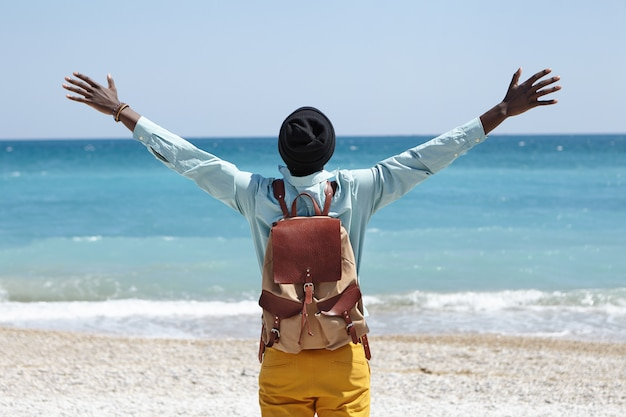 Read view of happy carefree african american male standing on beach in front of azure sea, spreading arms, feeling freedom and connection to amazing nature around him