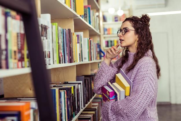 積極的に収集している読者。本棚の前にとどまりながら2冊の本から選ぶ思いやりのある前向きな女性
