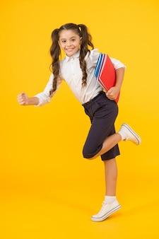 Читатель кидается за книгами. счастливая маленькая девочка держит книги с красочными крышками на желтом фоне. милый маленький ребенок улыбается с энциклопедией или ручными книгами. учебные книги для умных школьников.