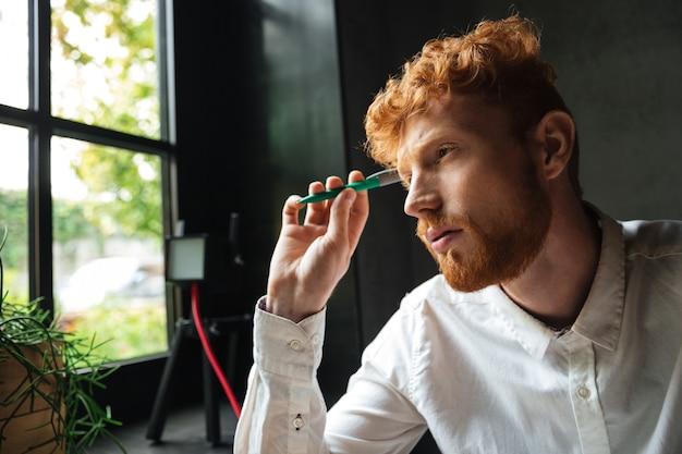 Портрет крупного плана молодого сконцентрированного readhead бородатого человека, держащ зеленую ручку, смотря окно