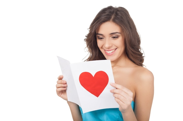 발렌타인 카드를 읽고. 흰색 배경에 고립 된 서있는 동안 발렌타인 데이 카드를 읽는 매력적인 젊은 여자