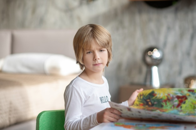 Reading activity. a fair-haired boy reading a magazine at home