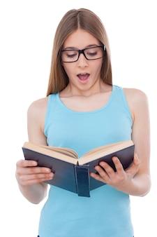 Чтение увлекательной книги. удивленная девочка-подросток, читающая книгу, стоя изолированной на белом